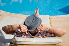 Man in a hat lying on a lounger by the pool Royalty Free Stock Photo
