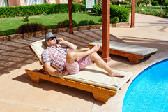 Man in a hat lying on a lounger by the pool Stock Photography