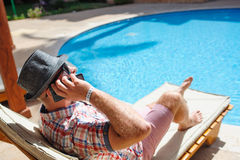 Man in a hat lying on a lounger by the pool and talking on the phone Stock Photos