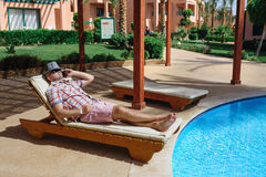 Man in a hat lying on a lounger and talking on the phone Royalty Free Stock Images