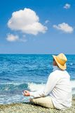 Man with hat meditation. In the beach Royalty Free Stock Photos