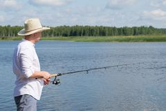 A man in a hat, outdoors, engaged in fishing on the pond stock photo