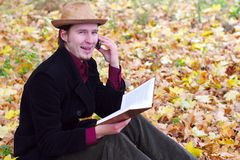 Man with hat, phone, book in autumn leaves Stock Image