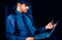 Man with Hat and Pipe Looking at Laptop Stock Photo