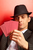 Man with hat playing poker. Focus on cards. Man with hat playing underground poker on rad background Royalty Free Stock Photos