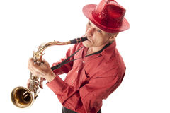 Man with hat playing saxophone. Male musician with hat playing a brass tenor saxophone from above Royalty Free Stock Photography