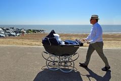 Man in hat pushing Vintage Pram along Seafront Promenade. royalty free stock photos