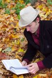 Man with hat reading book in autumn leaves Royalty Free Stock Image