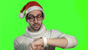 Man in the hat of Santa Claus using smartwatch touchscreen, cute smiles on a green background.  stock video