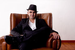 Man with hat seated on a chair Royalty Free Stock Image