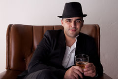 Man with hat seated on a chair Royalty Free Stock Images