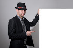 A man in a hat shows a finger on a blank billboard Stock Photo