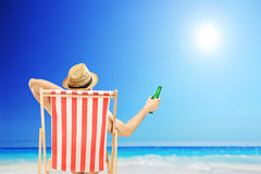 Man with hat sitting on a beach chair and holding a beer next to Stock Image