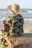 Man with hat sitting and looking at the ocean in Colombia Stock Image