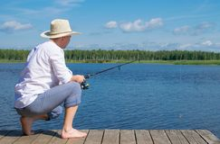 A man in a hat, sitting on the pier, holding a fishing rod and fishing, against the blue sky and the lake royalty free stock photos