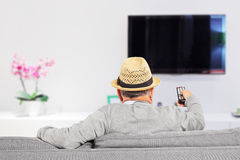 Man with hat sitting on a sofa and changing channels at home Royalty Free Stock Photography