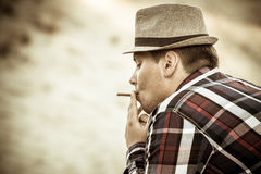 Man with hat smoking Stock Photo