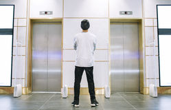 Man in hat standing near the elevator stock image