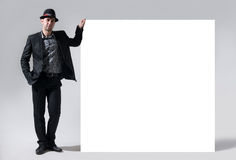 A man in a hat stands next to a blank billboard Royalty Free Stock Photography