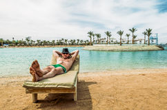 The man in the hat sunbathes on a lounge chair on the beach at a Stock Image