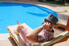 Man in hat sunbathing on the phone by the pool royalty free stock image