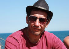 A man in a hat and sunglasses. Close-up on a background of blue sky Royalty Free Stock Photo