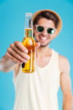 Man in hat and sunglasses giving you bottle of beer Royalty Free Stock Photography