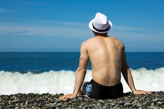 A man in a hat and swimming trunks by the sea. A man in a white hat and black trunks sits on a pebble by the sea Stock Photography