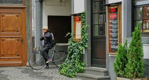Man in hat takes a break while sitting on bicycle in old town Cologne. Cologne, Germany - Aug 2015: Male 10 speed cyclist pauses on his bike in alley entrance in stock images