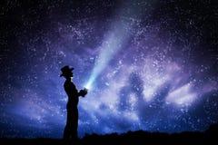Man in hat throwing light beam up the night sky full of stars. To explore, dream, magic. Stock Image