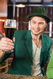 Man with a hat toasting a beer Stock Images