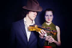 Man in hat with violin and young woman in veil. Young man in hat with violin and young woman in veil with bouquet of roses on black background Royalty Free Stock Photo