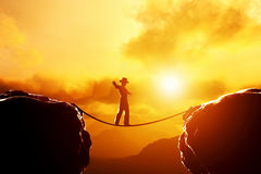 Man in hat walking, balancing on rope over mountains. Man in hat walking and balancing on rope over precipice in mountains at sunset. Concept of business, risk Stock Images