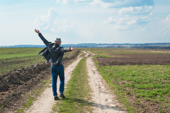 Man in a hat walking on a dirt road in a field royalty free stock image