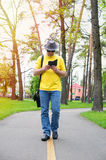 Man in hat is walking in the park with phone. Man with hat is walking in the park with phone Royalty Free Stock Photo