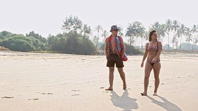 Man in Hat and Woman with Long Hair in Swimsuit Walk on Beach stock video