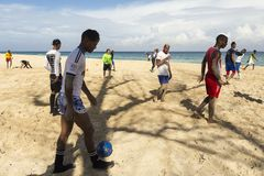 Cuban soccer player walking on beach and pushing ball with a relaxed attitude stock photos