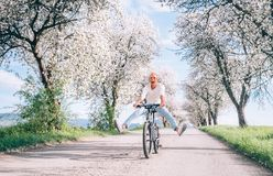Man have fun when rides a bicycle on country road Stock Image