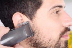 Man having a beard cut with hair clippers. Stock Photos