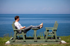 Young man sitting on the bench Royalty Free Stock Photography