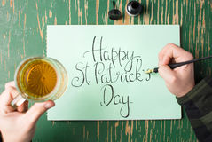 Man having a beer with Happy St Patrick day card. Man having a beer with Happy St Patrick day calligraphy card Royalty Free Stock Images