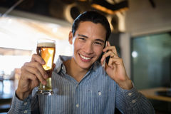 Man having beer while talking on mobile phone Stock Photos