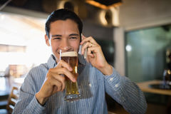 Man having beer while talking on mobile phone Stock Images