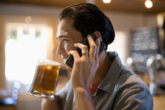 Man having beer while talking on mobile phone in a restaurant Royalty Free Stock Photography