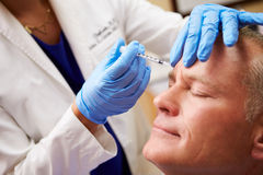 Man Having Botox Treatment At Beauty Clinic. With Beautician Using Syringe royalty free stock image