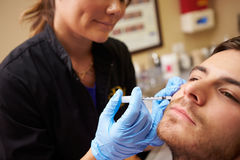 Man Having Botox Treatment At Beauty Clinic. By Beautician Wearing Gloves royalty free stock images