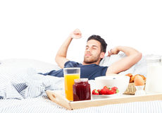 Man is having breakfast in the bed Royalty Free Stock Photography