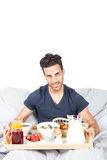 Man is having breakfast in the bed Stock Photography