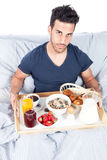 Man is having breakfast in the bed Stock Photos
