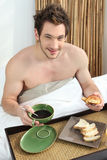 Man having breakfast in bed Stock Images